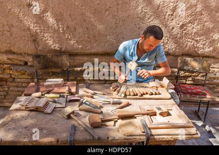 An artist carving the wood in Khiva, Uzbekistan. - Stock Photo