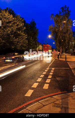 Blue and orange urban night scene with a motion-blurred speeding traffic passing a give way markings in the foreground, - Stock Photo
