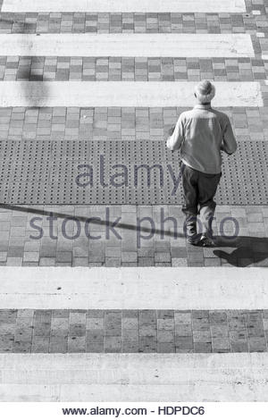 Black and white image of an elderly man on a pedestrian crossing, viewed from above. Goods Way to Granary Square, - Stock Photo