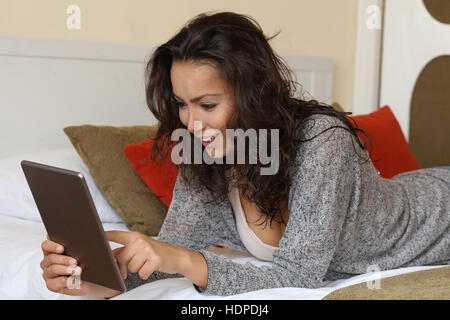 woman checking tablet at home lying on bed - Stock Photo