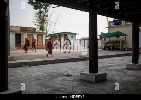 Young novice Buddhist monks playing football at the Shwe Yan Pyay Monastery in Nyaungshwe, Myanmar. - Stock Photo