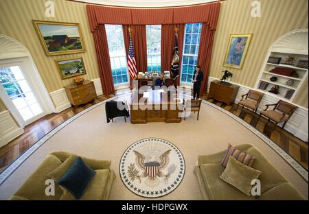 U.S. President Barack Obama talks on the phone on Thanksgiving Day at the White House Oval Office November 24, 2016 - Stock Photo