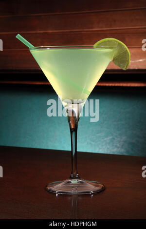 appletini cocktail with lime wheel, vodka, pineapple juice, liqueur in classic martini cocktail glass - Stock Photo