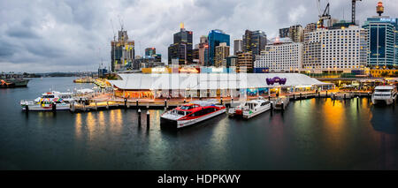 Gray sky and golden light in Sydney Darling harbour - Stock Photo