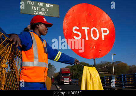 A woman controls the traffic between Zambia and Zimbabwe.  A STOP sign indicates that we are entering Zambia. Today - Stock Photo