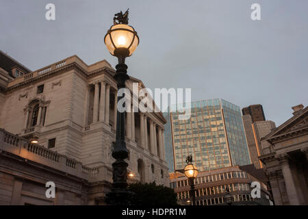 Early evening lighting illuminates the street, below the Bank of England, on 9th December 2016, in the City of London. - Stock Photo