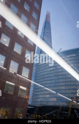 A scene of urban architecture at London Bridge with the Shard riding high above, and with diagonal lighting from - Stock Photo