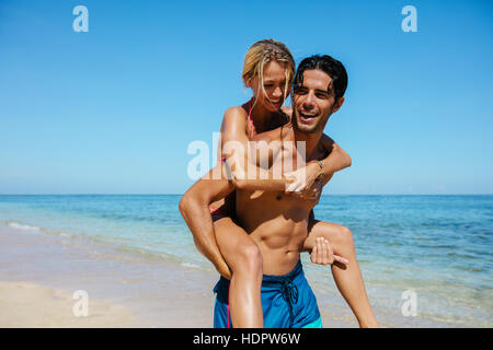 Portrait of man carrying girlfriend on his back. Couple enjoying piggyback ride on the beach vacation. - Stock Photo