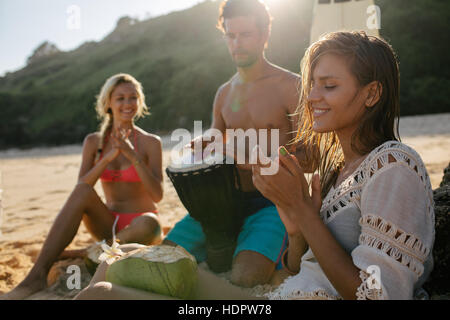 Young woman enjoying holidays with her friends on the beach. Women clapping and man playing dumbek. - Stock Photo
