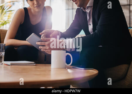 Cropped shot of businessman and businesswoman having a meeting in office lobby using digital tablet. Office workers - Stock Photo