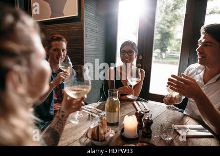 Indoor shot of young friends drinking wine at cafe. Group of men and women enjoying a glass of wine at restaurant. - Stock Photo