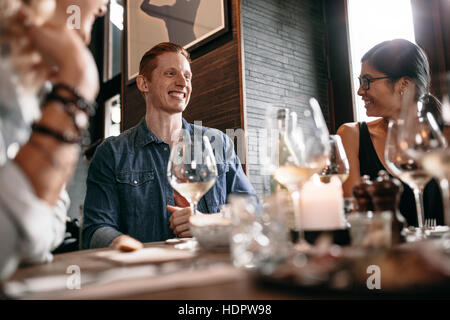 Happy young man with friends at cafe. Young people enjoying dinner at a restaurant. - Stock Photo