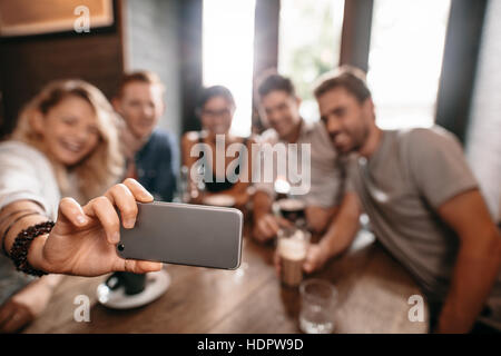 Group of young people taking a selfie at cafe. Young friends at restaurant taking self portrait. - Stock Photo