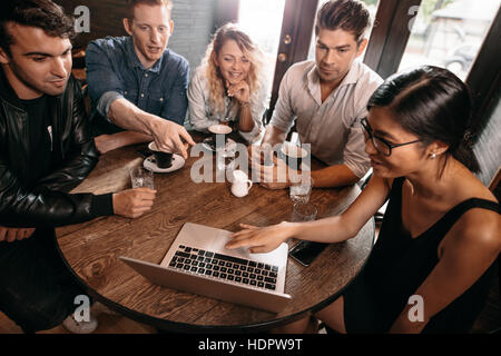 Diverse group of friends sitting together at cafe with man pointing at laptop. Five young people hanging out at - Stock Photo