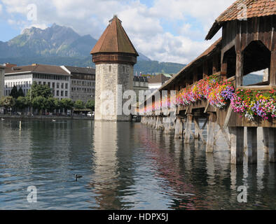 Famous Chapel Bridge and Mount Pilatus in Lucerne, Switzeland on a clear summer day. - Stock Photo