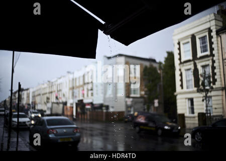 Drops of water falling from shop awning on a gloomy urban daylight rain storm - Stock Photo