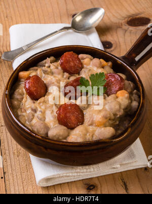 bean stew with sausage on wooden table in rustic setting - Stock Photo