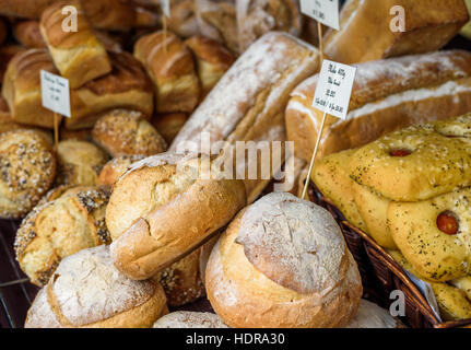 Crusty fresh bread on sale at a market stall. - Stock Photo