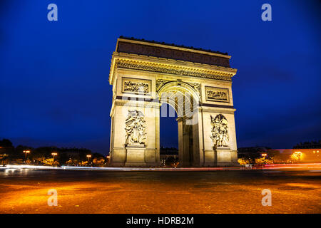 The Triumphal Arch (Arc de Triomphe) in Paris, France at night - Stock Photo