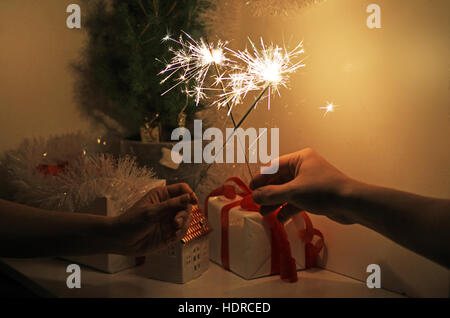 Christmas sparklers in darkness. - Stock Photo