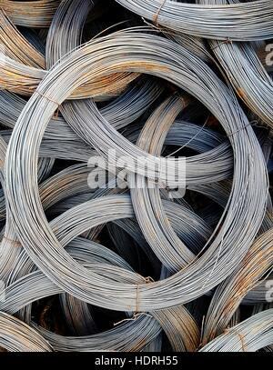 Coils of old galvanized wires with traces of rust - Stock Photo