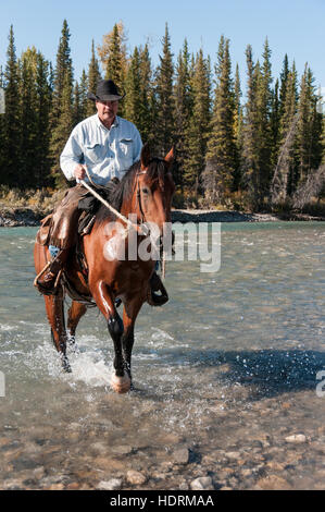 Cowboy and horse crossing river, Clearwater county; Alberta, Canada - Stock Photo