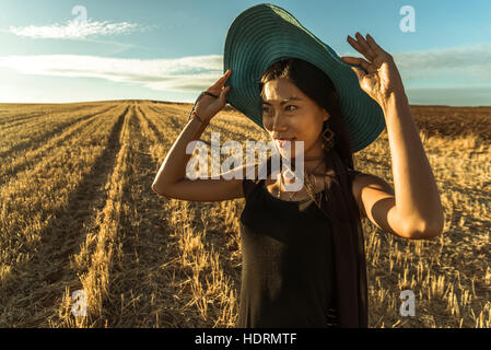 Chinese young woman walking in a wheat field; Madrid Spain - Stock Photo