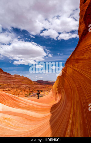 View of a hiker in the sandstone formation known as the Wave, Vermillion Cliffs; Arizona, United States of America - Stock Photo