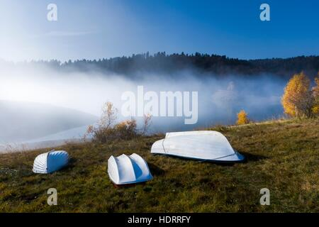 Three White boats ashore lying inverted on shore morning fog triple - Stock Photo