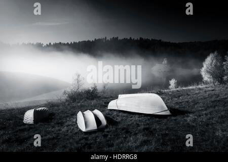 Three White boats ashore lying inverted on shore morning fog lake calmness fog magic atmospheric scenic - Stock Photo