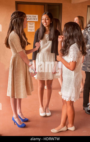 Hispanic teenage girls socialize as they wait for Confirmation mass at a Laguna Niguel, CA, Catholic church. Note - Stock Photo