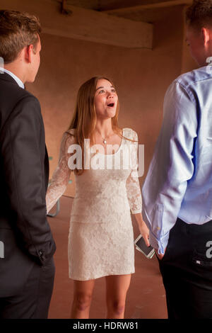 Wearing a white formal dress, a teenage girl socializes while waiting for Confirmation mass at a Laguna Niguel, - Stock Photo