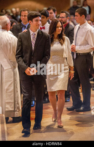 Formally dressed teens participate in Confirmation mass at a Laguna Niguel, CA, Catholic church. Note white dress. - Stock Photo