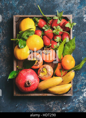 Oranges, lemons, pomegranate, bananas, strawberries and persimmon in wooden box - Stock Photo