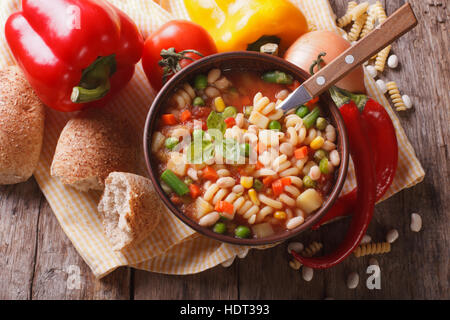 Italian vegetable minestrone soup in a bowl and ingredients on the table. horizontal view from above close-up - Stock Photo
