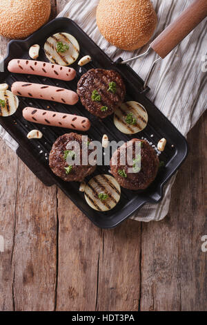 grilled hamburgers and hot dogs on the grill pan. vertical top view - Stock Photo