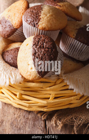Delicious chocolate orange muffins in a basket close-up, vertical - Stock Photo