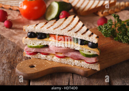 Sandwich with ham, cheese and vegetables on the chopping board and ingredients on the table. horizontal - Stock Photo