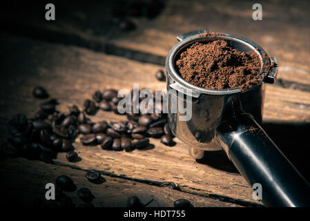 Ground coffee in porta filter holder on the wooden surface with beans dropped loosely - Stock Photo