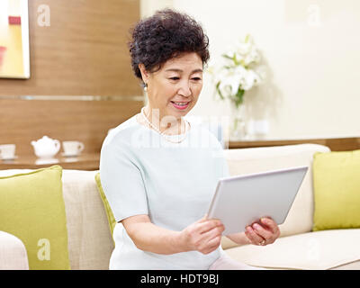 senior asian woman sitting on couch looking at tablet computer - Stock Photo