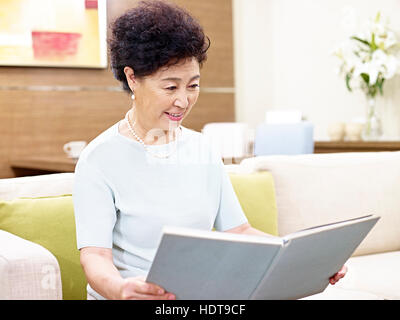 senior asian woman sitting on couch reading a book - Stock Photo