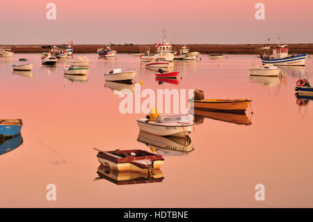 Fisher boats anchoring in the calm waters of lagoon Ria Formosa at twilight - Stock Photo