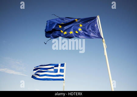 Ripped european Union flag and Greek flag, waving in the wind - Stock Photo
