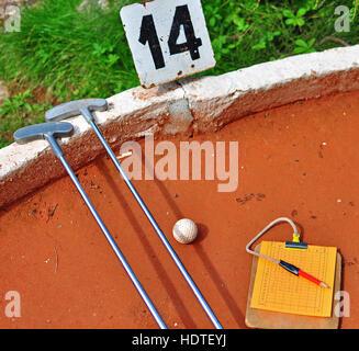 Two sticks and ball, mini golf scene - Stock Photo