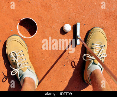 Mini golf scene, stick and ball at the hole - Stock Photo