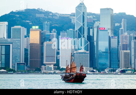 Traditional Chinese Junk Boat on Victoria Harbour and Hong Kong Skyline, China, Asia. - Stock Photo