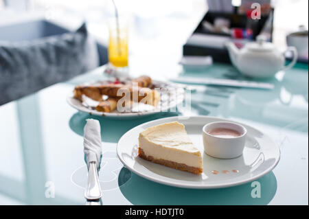 Slice of cheesecake on white plate and glass table in cafe - Stock Photo