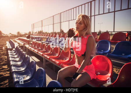 Attractive female runner seated on the beach resting after intensive volleyball game, the summer background - Stock Photo