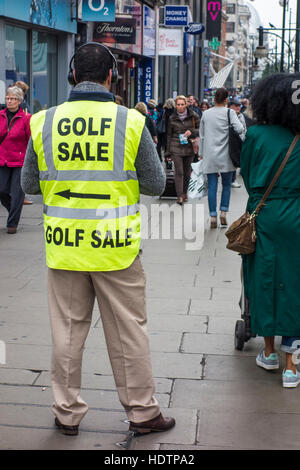 Shoppers passing man wearing high visibility jacket with Golf Sale advertising sign. Oxford Street, London - Stock Photo