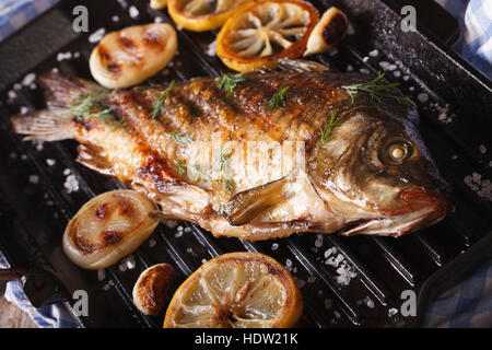 Close up of whole fish garlic and tomato cooking for Pan grilled fish